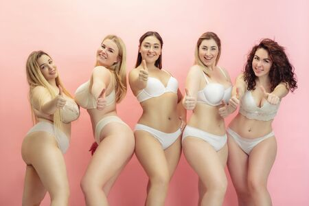 In love with myself. Portrait of beautiful plus size young women posing on pink gradient background. Happy female models having fun together. Concept of body positive, beauty, fashion, style, feminism.