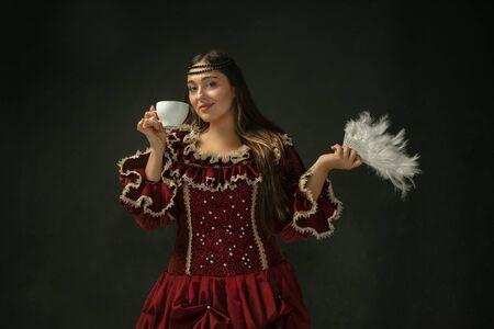 Beber café, sostiene un ventilador esponjoso. Mujer joven medieval en ropa vintage roja sobre fondo oscuro. Modelo femenino como duquesa, persona real. Concepto de comparación de épocas, moderno, moda, belleza. Foto de archivo