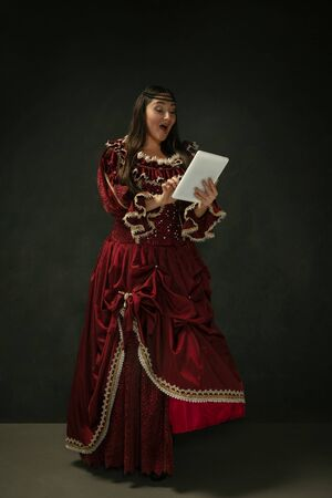 Astonished. Portrait of medieval young woman in red vintage clothing using tablet on dark background. Female model as a duchess, royal person. Concept of comparison of eras, modern, fashion, beauty.