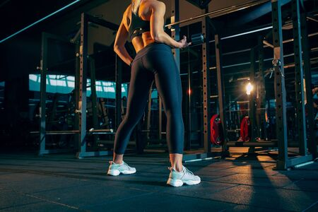 Calm. Young muscular caucasian woman practicing in gym with the weights. Athletic female model doing strength exercises, training her upper, lower body. Wellness, healthy lifestyle, bodybuilding. Фото со стока