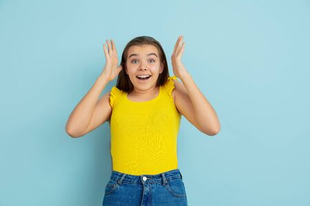 Astonished, shocked. Caucasian teen girls portrait isolated on blue background. Beautiful model in casual yellow wear. Concept of human emotions, facial expression, sales, ad. Copyspace. Looks cute. Banque d'images - 140079448