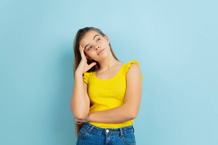 Thoughtful. Caucasian teen girls portrait isolated on blue background. Beautiful model in casual yellow wear. Concept of human emotions, facial expression, sales, ad. Copyspace. Looks cute.