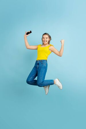 Jumping high with smartphone. Caucasian teen girls portrait on blue background. Beautiful long hair model in casual. Concept of human emotions, facial expression, sales, ad. Copyspace. Looks cute. Banque d'images - 140095377