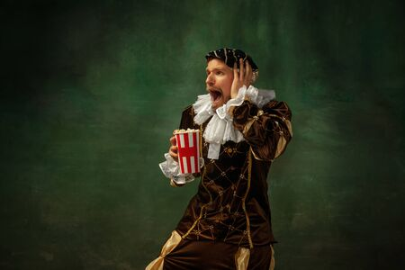 Emotional watching soccer. Portrait of medieval young man in vintage clothing standing on dark background. Male model as a duke, prince, royal person. Concept of comparison of eras, modern, fashion. Archivio Fotografico