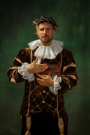 Skins smell. Business. Portrait of medieval young man in vintage clothing standing on dark background. Male model as a duke, prince, royal person. Concept of comparison of eras, modern, fashion.