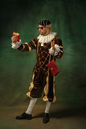 Delicious fried potato. Portrait of medieval young man in vintage clothing with wooden frame on dark background. Male model as a prince, royal person. Concept of comparison of eras, modern, fashion.