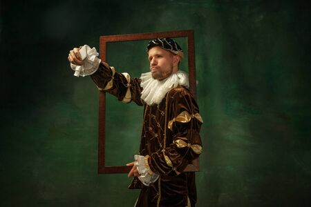 Selfie-time. Portrait of medieval young man in vintage clothing with wooden frame on dark background. Male model as a duke, prince, royal person. Concept of comparison of eras, modern, fashion.