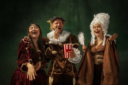 Funny cinema. Portrait of medieval young people in vintage clothing on dark background. Models as a duke and duchess, princess, royal persons. Concept of comparison of eras, modern, fashion.