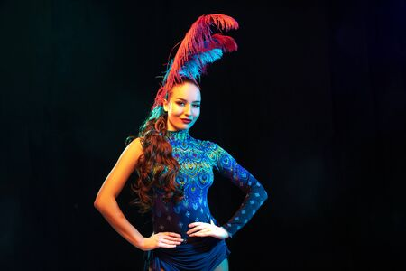 Mystically. Beautiful young woman in carnival, stylish masquerade costume with feathers on black background in neon light. Copyspace for ad. Holidays celebration, dancing, fashion. Festive time, party.