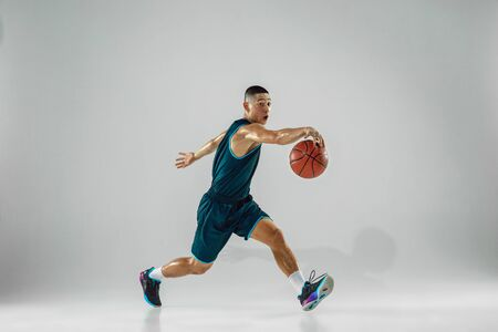 Young basketball player of team wearing sportwear training, practicing in action, motion in run isolated on white background. Concept of sport, movement, energy and dynamic, healthy lifestyle.