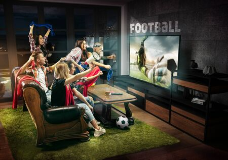 Group of friends watching TV, match, championship, sport games. Emotional men and women cheering for favourite team, look on fighting for ball. Concept of friendship, sport, competition, emotions. Banque d'images