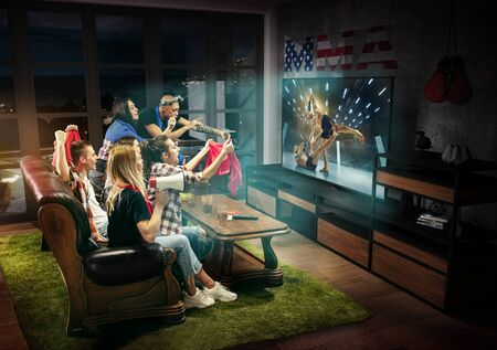 Group of friends watching TV, match, championship, sport games. Emotional men and women cheering for favourite MMA fighter of America with flag. Concept of friendship, sport, competition, emotions.