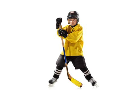 Little hockey player with the stick on ice court and white studio background. Sportsboy wearing equipment and helmet practicing, training. Concept of sport, healthy lifestyle, motion, movement, action.