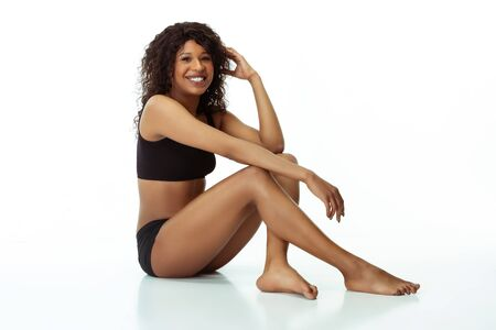 Smiling, beautiful, feminine. Slim tanned woman isolated on white studio background. African-american model with well-kept shape and skin. Beauty, self-care, weight loss, fitness, slimming concept. Stockfoto