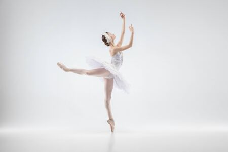 Anmutige klassische Ballerina tanzen isoliert auf weißem Studiohintergrund. Frau in zarter Kleidung wie Charaktere eines weißen Schwans. Das Konzept Anmut, Künstler, Bewegung, Aktion und Bewegung. Sieht schwerelos aus.