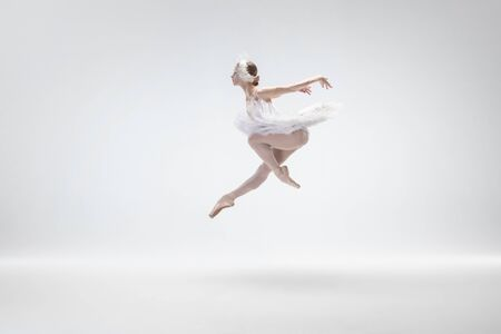 Flying bird. Graceful classic ballerina dancing isolated on white studio background. Woman in tender clothes like a white swan characters. The grace, artist, movement, action and motion concept.