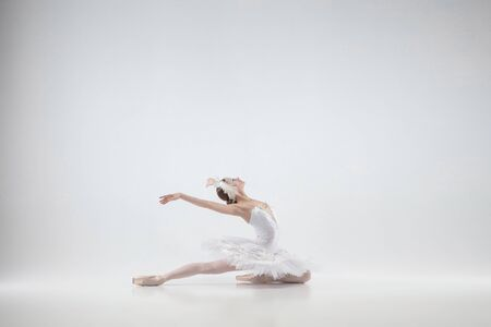 Big scene. Young graceful classic ballerina dancing on white studio background. Woman in tender clothes like a white swan. The grace, artist, movement, action and motion concept. Looks weightless.