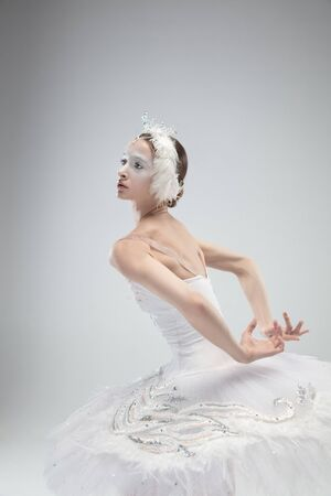Close up of graceful classic ballerina dancing on white studio background. Woman in tender clothes like a white swan. The grace, artist, movement, action and motion concept. Looks weightless. Banque d'images