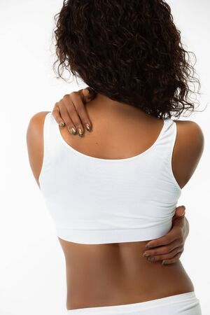 Spine and back. Slim tanned womans back on white studio background. African-american model with well-kept shape and skin. Beauty, self-care, weight loss, fitness, slimming concept. Healthcare.