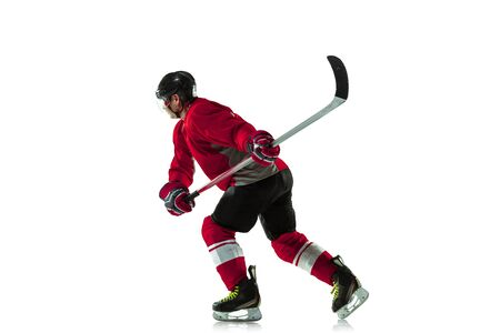 Scoring a goal. Male hockey player with the stick on ice court and white background. Sportsman wearing equipment and helmet practicing. Concept of sport, healthy lifestyle, motion, movement, action. Standard-Bild - 140645627