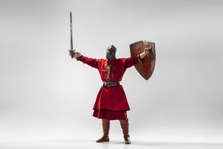 Brave armored knight with professional weapon fighting isolated on white studio background. Historical reconstruction of native fight of warriors. Concept of history, hobby, antique military art.
