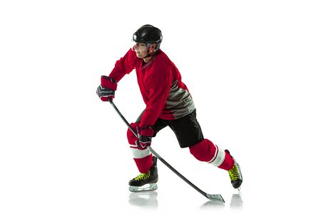 Leader. Male hockey player with the stick on ice court and white background. Sportsman wearing equipment and helmet practicing. Concept of sport, healthy lifestyle, motion, movement, action.