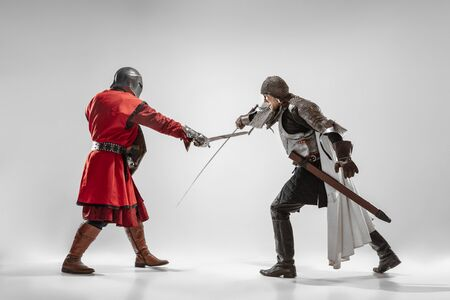 Brave armored knights with professional weapon fighting isolated on white studio background. Historical reconstruction of native fight of warriors. Concept of history, hobby, antique military art.