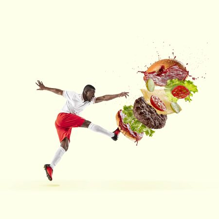 Soccer player kicking burger like ball in jump on yellow background. Copyspace for ad. Modern design. Contemporary artwork, collage. Concept of sport, food, delicious, business, action, motion.