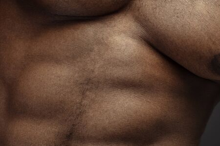 Belly. Detailed texture of human skin. Close up shot of young african-american male body. Skincare, bodycare, healthcare, hygiene and medicine concept. Looks beauty and well-kept. Dermatology.