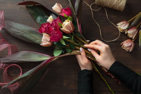 Florist at work: woman making fashion modern bouquet of different flowers on wooden background. Masterclass. Gift for bride on wedding, mothers, womans day. Romantic spring fashion. Passion roses.