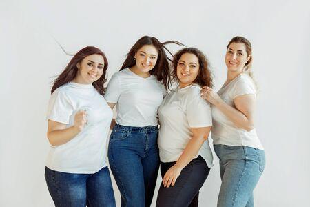 Beau. Jeunes femmes de race blanche en tenue décontractée s'amusant ensemble. Des amis posant sur fond blanc et riant, ont l'air heureux, bien entretenus. Bodypositive, féminisme, s'aimer, concept de beauté.