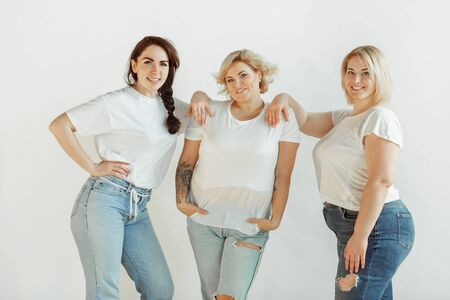 Team. Young caucasian women in casual clothes having fun together. Friends posing on white background and laughting, looks happy, well-kept. Bodypositive, feminism, loving themself, beauty concept.