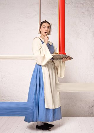 Medieval young woman as a medieval lady milkmade on white studio background. Trying fast food, fried potato. Concept of comparison of eras. Stylish creative design, art vision, new look of artwork. Banque d'images