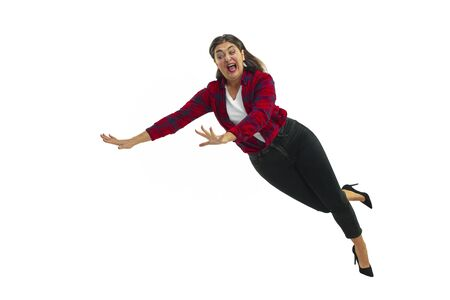 A second before falling. Caucasian young girl falling down in moment with bright emotions and facial expression. Female model in casual clothes. Shocked, scared, screaming. Copyspace for ad.
