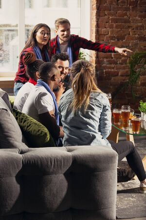 Excited group of people watching football, sport match at home. Multiethnic group of friend, fans cheering for favourite national basketball, tennis, soccer, hockey team. Concept of emotions, support.