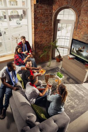 Excited group of people watching american football, sport match at home. Multiethnic group of emotional friend, fans cheering for favourite national team, drinking beer. Concept of emotions, support.
