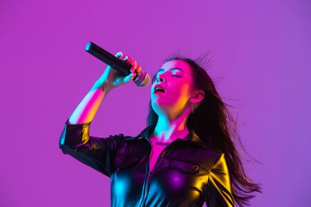 Caucasian female singer portrait isolated on purple studio background in neon light. Beautiful female model in black wear with microphone. Concept of human emotions, facial expression, ad, music, art. Stock Photo