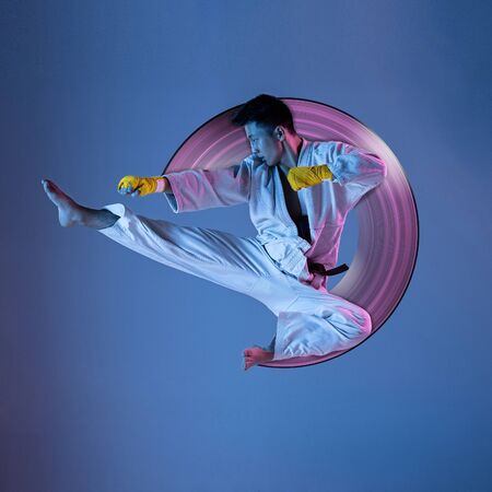 Concept of motion and action in sport. Confident korean man in kimono practicing hand-to-hand combat, martial arts. Blue background, neon light. Sport, healthy lifestyle, movement. Abstract design.