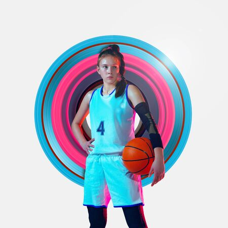 Concept of motion and action in sport. Full length portrait of female basketball player with a ball on background. Confident teenager. Motion, activity, movement, ad, wellness. Abstract design. Stock Photo