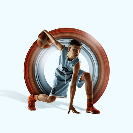Concept of motion and action in sport. Full length portrait of a basketball player with a ball on background. Caucasian teen athlete in jump. Motion, activity, movement, advertising. Abstract design. Stock Photo