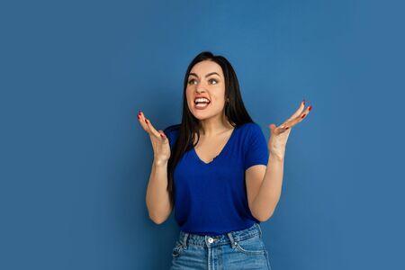 Des cris de colère et de folie. Portrait de belle femme caucasienne sur fond bleu studio. Beau modèle de femme brune en casual. Concept d'émotions humaines, expression faciale, ventes, publicité, copyspace. Banque d'images