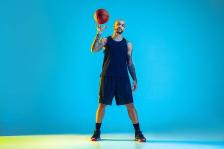 Young basketball player of team wearing sportwear training, practicing in action, motion isolated on blue background in neon light. Concept of sport, movement, energy and dynamic, healthy lifestyle.