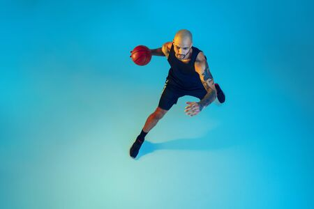 Top view. Young basketball player of team wearing sportwear training, practicing in action, motion on blue background in neon light. Concept of sport, movement, energy and dynamic, healthy lifestyle.