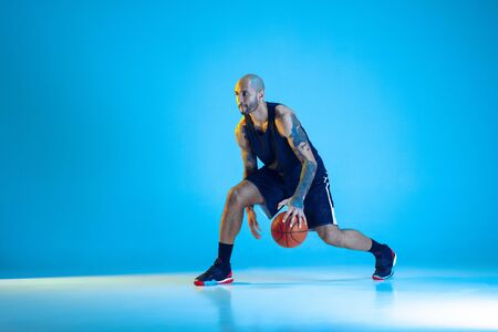 Young basketball player of team wearing sportwear training, practicing in action, motion isolated on blue background in neon light. Concept of sport, movement, energy and dynamic, healthy lifestyle. Reklamní fotografie