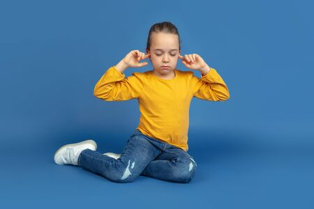 Portrait of sad little girl sitting isolated on blue studio background. How it feels to be autist. Modern problems, new vision of social issues. Concept of autism, childhood, healthcare, medicine.