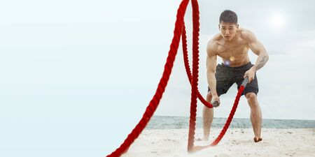 Young healthy man, athlete doing exercise with the ropes at the beach. Male model training hard his upper body. Concept of healthy lifestyle, sport, fitness, bodybuilding, wellness. Flyer, copyspace.