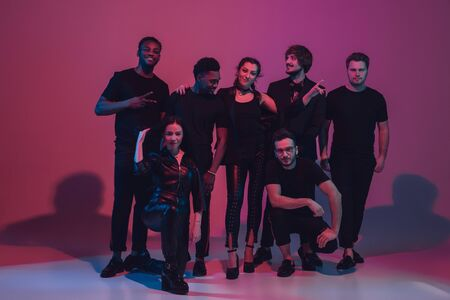 Group of young multiethnic musicians created band, dancing in neon light on pink background. Concept of music, hobby, festival, wellness. Joyful party host, dancer, singer, guitarist, saxophonist.