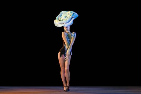 Delighted. Young female dancer with huge floral hat in neon light on black background. Graceful model, woman dancing, posing. Concept of carnival, beauty, motion, blooming, spring fashion.