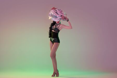 Delighted. Young female dancer with huge floral hats in neon light on gradient background. Graceful model, woman dancing, posing. Concept of carnival, beauty, motion, blooming, spring fashion. Banque d'images
