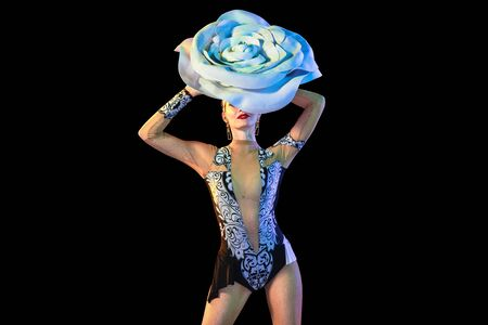 Tender and bloom. Young female dancer with huge floral hat in neon light on black background. Graceful model, woman dancing, posing. Concept of carnival, beauty, motion, blooming, spring fashion.